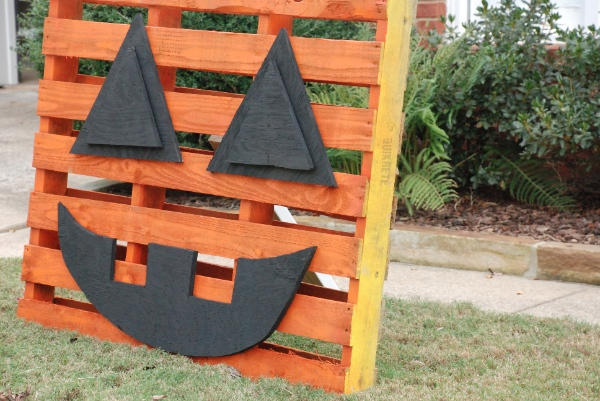 A pallet decorated like a pumpkin for halloween decorations